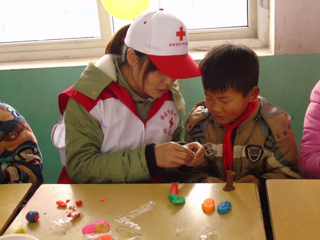 在一间教室,小朋友们将折的爱心,篮子,青蛙和纸飞机送给志愿者;另一间
